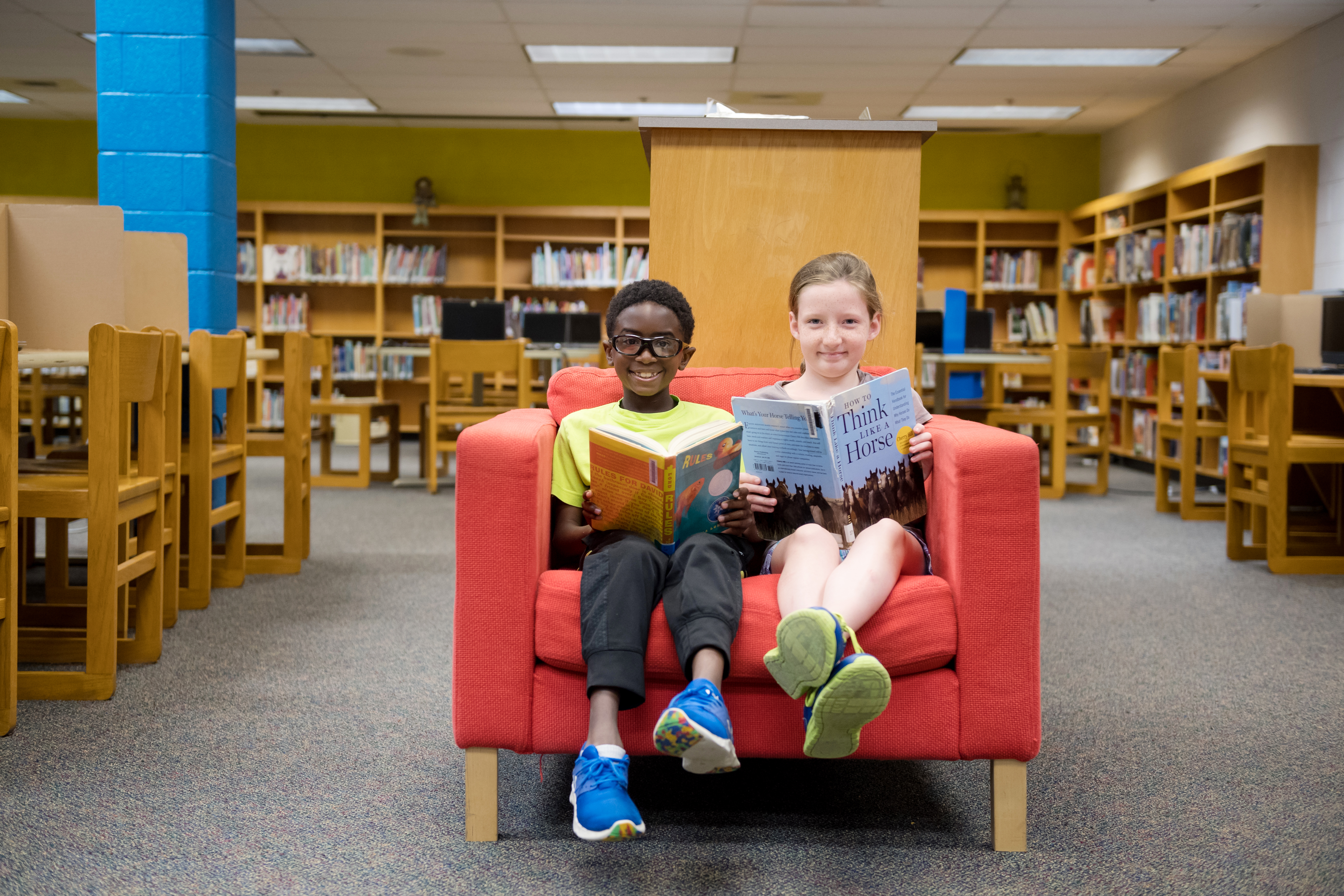 photo of two students in a chair with books in the library