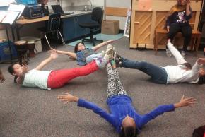photo of students on floor making a plus shape with bodies